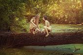 picture of wench  - On a tree in the forest sitting wild man and woman and looking at each other - JPG