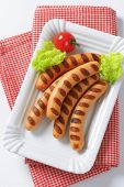 grilled hot dog sausages with lettuce and tomato on paper plate and chequered napkin