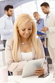 Happy blonde woman using tablet computer at workplace, smiling.