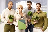 Happy young businesspeople smiling at camera, holding green plants in hand.