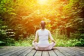 picture of breathing exercise  - Young woman meditating in a forest sitting on a wooden floor - JPG