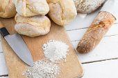 Ciabatta bread on wooden cutting board with knife.