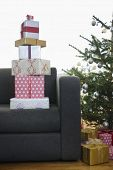 Stack of Christmas presents on sofa