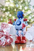 Retro style toy robot in front of Christmas tree