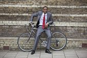 Portrait of a happy young businessman with bicycle against brick wall