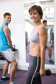 Fit couple lifting weights together smiling at camera at the gym