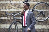 Portrait of African American businessman carrying Bicycle
