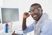 Hipster businessman smiling at camera at his desk in his office