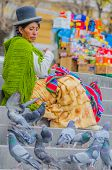 LA PAZ, BOLIVIA, MAY 9, 2014 - Local woman in traditional costume and bowler hat sits on stairs on P