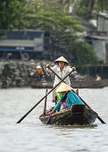 One Women Rower Stands On Her Simple Rowboat.