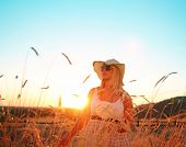 a pretty woman standing in a field at sunrise or sunset