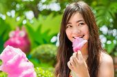 Cute Thai Girl Is Eating Pink Candyfloss With Joy.
