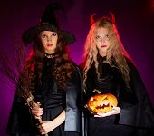 Portrait of two sullen females with broom and pumpkin looking at camera