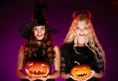 picture of antichrist  - Portrait of two happy females with pumpkins looking at camera with smiles - JPG