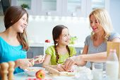 Portrait of happy girls helping their mother to cook pastry