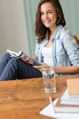 Smiling teenage girl reading magazine at home sitting by wooden table