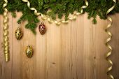 Christmas Wooden Background with fir tree, golden ribbon and decorations like pine cones