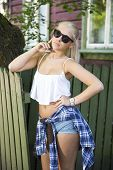 Cute young blonde girl in front of wooden house