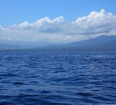 Blue tropical sea with waves and land with mountains ( Lombok island)
