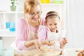 Grandmother And Granddaughter Making Dough