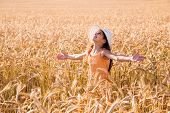 Happy girl on wheat field