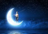 Boy of school age with fishing rod at night