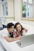 Young happy couple sharing laptop on sofa