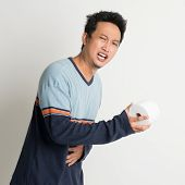Asian male stomach pain holding toilet paper running to toilet, with painful face expression, on plain background