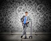 Young determined businessman leaning on wrench and cogwheels at background