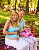 Pregnant woman, holding gift box with man outdoor.