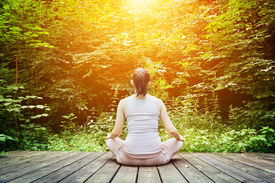 stock photo of breathing exercise  - Young woman meditating in a forest sitting on a wooden floor - JPG