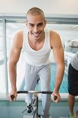 Portrait of a handsome young man working out on exercise bike at the gym
