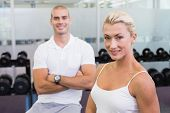 Portrait of a sporty young couple standing at fitness studio