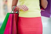 Female customer in smart casual carrying colorful paperbags