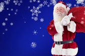 Santa carries his red bag and smiles against blue