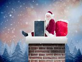 Santa sits leaned on his bag with a board against twinkling stars