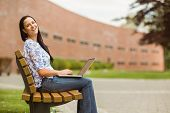 Happy brown hair sitting on bench using laptop in the park