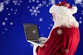 Santa Claus uses a laptop against blue