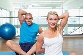 Portrait of happy young couple stretching hands behind back in yoga class
