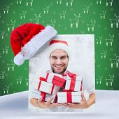 festive man holding christmas gifts against green reindeer pattern