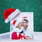 festive young couple holding gift against green christmas tree pattern