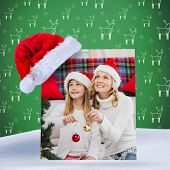 Festive mother and daughter decorating christmas tree against green reindeer pattern