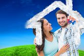 Happy young couple showing new house key against green hill under blue sky