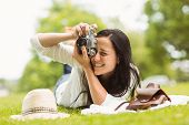 Happy brunette lying on grass taking picture in the park
