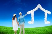 Happy hipster couple holding hands and looking against green field under blue sky