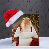 Relaxed santa writing list with a quill against grey reindeer pattern