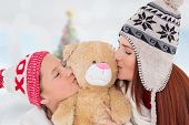Mother and daughter kissing teddy against blurry christmas tree in room