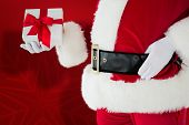 Mid section of santa holding gift against red snowflake background