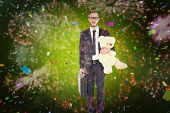Geeky businessman holding briefcase and teddy against colourful fireworks exploding on black background