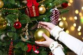 Child's hands hanging bauble on Christmas tree on bright background
